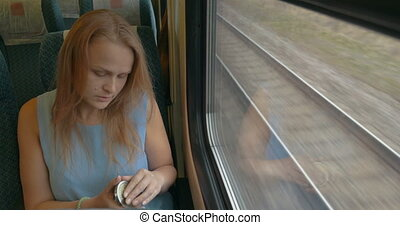Woman with Pocket-Glass in Train - High-angle shot of young...