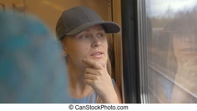 Female Photographer Traveling by Train - Young woman in cap...