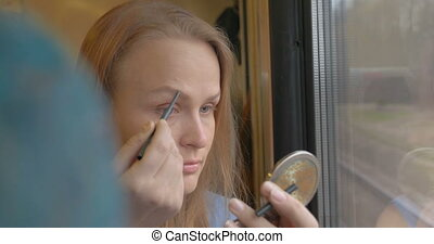 Woman going by train and putting on make-up - Young blonde...