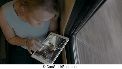 Young girl with tablet PC looking at photos in train - Top...