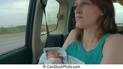 Young Mother Holding Newborn In The Car - Young caucasian...