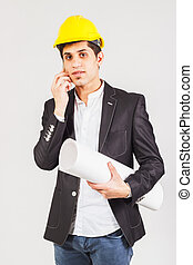 Worker with a blueprint talking by the phone - Young worker...