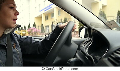 Short hair blond woman driving a car in the city