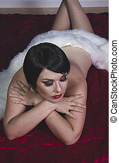 Lady beautiful brunette girl with short hair lying on a deep red fabric