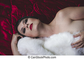 Sexy beautiful brunette girl with short hair lying on a deep red fabric