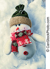 Christmas decorative snowman on the snow background