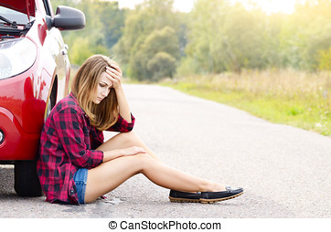 Young woman near broken car - Young woman sitting near...