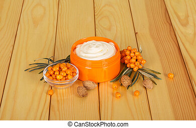 Jar with sea buckthorn cream on a wooden background