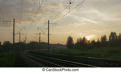 Passenger train in rural area at sunset