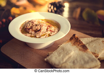 Plate with hummus dip and pita bread, a common tapas or...