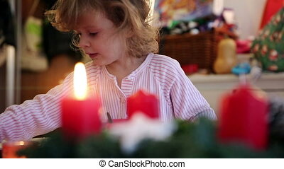 Candle with child in background on advent first - Playing...