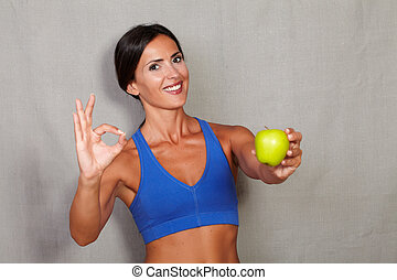 Satisfied lady showing apple and ok sign in fitness sport...