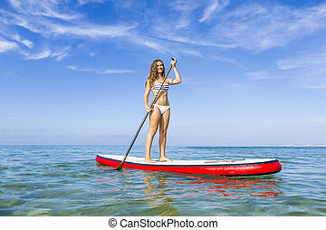 Woman practicing paddle - A beautiful woman practicing...