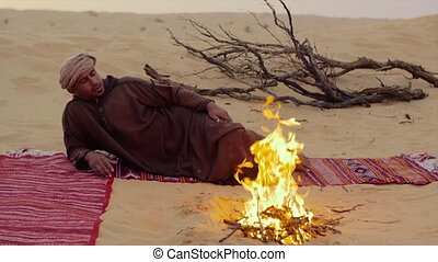a man camping in the sahara desert - sahara man near a fire