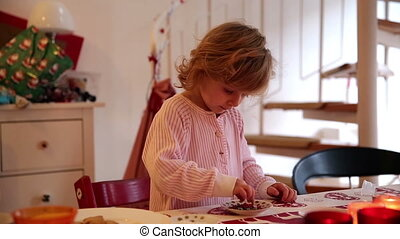 Close up of girl decorating cookies with her mother on...
