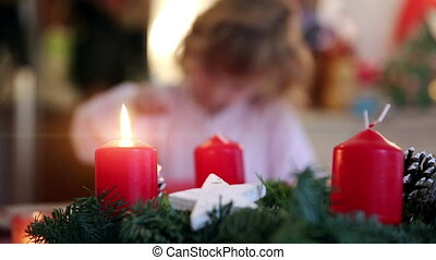 Burning candle and girl in background on advent first -...
