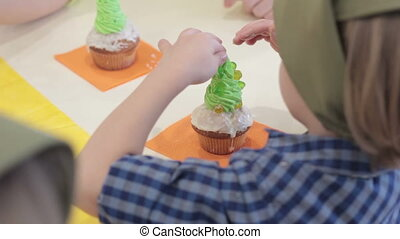Cupcakes little boy decorate with sprinkles muffins with...