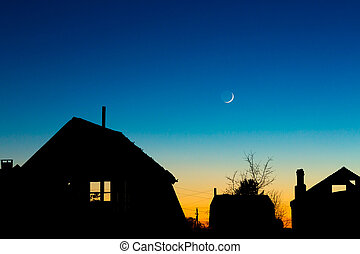 Roofs silhouettes against the night sky with new moon -...