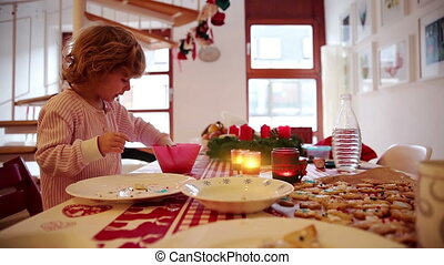 Girl helping with cookie preparation on advent first - A...
