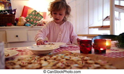 Girl with cookies at home on advent first - A little girl...