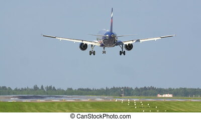 Plane landing on runway - Back view of an airplane getting...