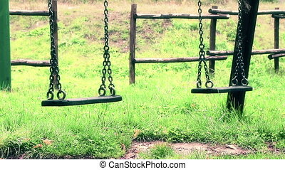 empty swings with chains swaying - old vintage empty swings...