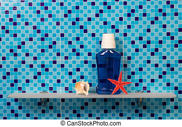 Bath mouthwash bottle, shell and starfish on blue background