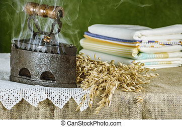 Old Hot Iron and Bunch of Oats on the Table