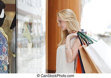 Woman looking at showcase - Woman with paper bags looking at...