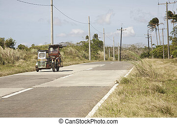 Motor tricycle - Lone motor tricycle on a road in the...