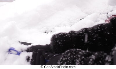 Girl cleans a car from the snow. A lot of snow. Car...