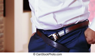 Belt wedding dressed - Seriuos man adjusts belt wedding...