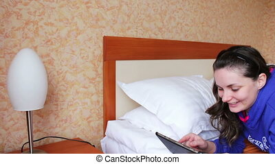 Woman with the tablet on the double bed.