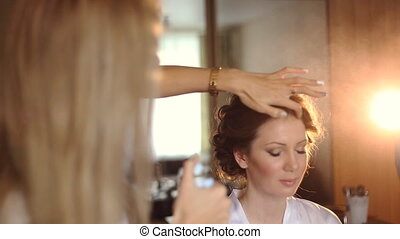 Beautiful bride applying wedding hairstyle