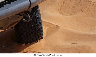 car stuck in sand during a rally, close up of a tire