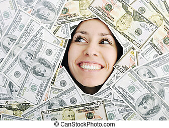 woman looking trought hole on money bacground - happy young...