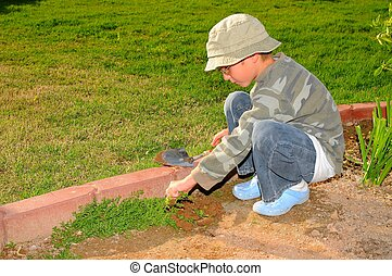 Young Boy Gardening - Young boy pulling weeds in a garden