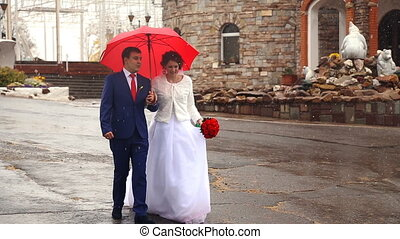 Wedding couple holding red umbrella in a rainy weather