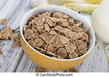 Wholemeal Cornflakes in a bowl on wooden background