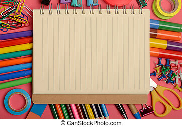 Notebook with stationary office supply on pink background