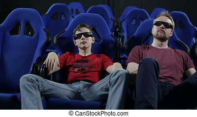People in stereo glasses sit at cinema watch movie