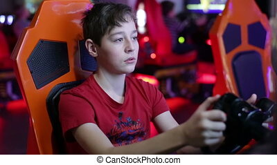 Teen playing on a slot machine simulator races - Teenager...