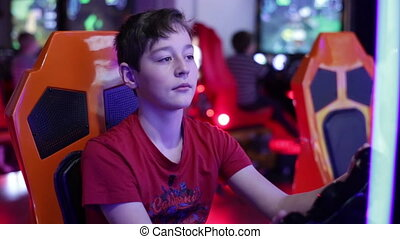 Boy playing on a slot machine simulator races - Teenager...