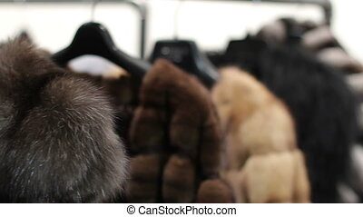 Mink coats hanging in the shop window. Shop mink coats....