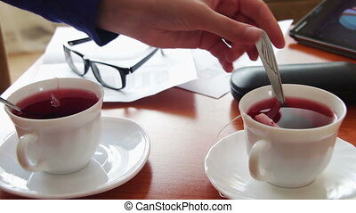 Woman pours tea for a business lunch - Woman holding a...