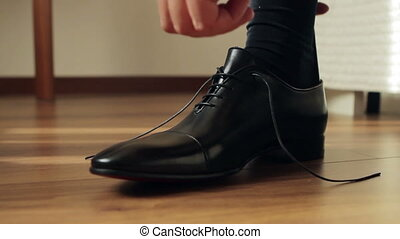 Business man tying the laces on shoes. Businessman dress...