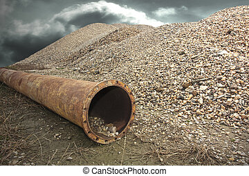 Drain pipe - Rusty industrial drain pipe next to a pile of...
