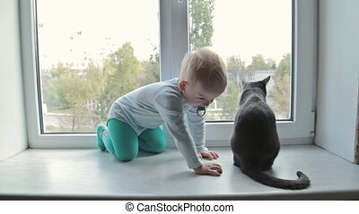 Little boy with black cat sitting near window at home