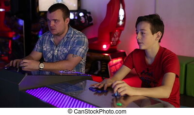 Father and son playing on slot machine simulator - The young...