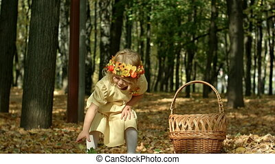 Cute girl with a basket full at the autumn park. Shot on...